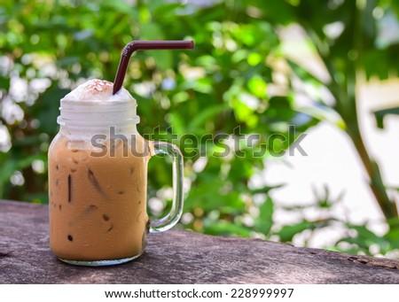 Iced coffee in  jug, jar, mug glass cups on the table. - stock photo