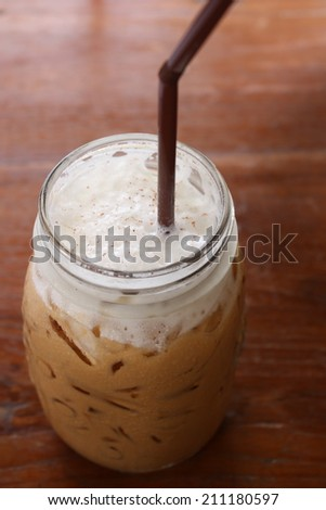 iced coffee in vintage glass on wooden plate and table. iced cappuccino. home-made iced cappuccino. homemade cappuccino. - stock photo