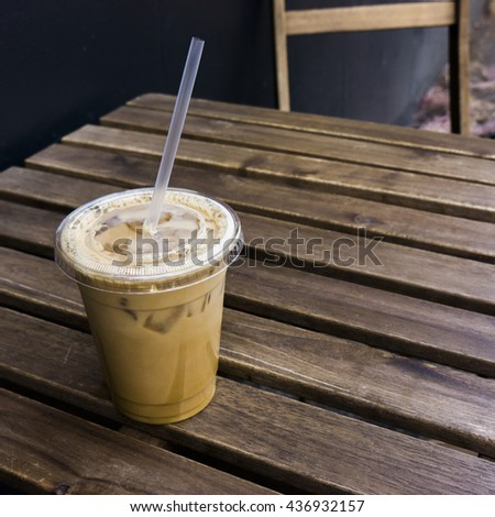 Iced coffee sitting on a wooden table in the shade on a hot day - stock photo