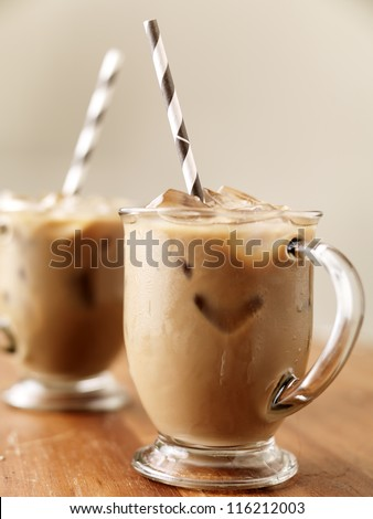 Iced coffee with black striped paper straw - stock photo
