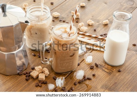 Iced coffee with milk in vintage jar - stock photo