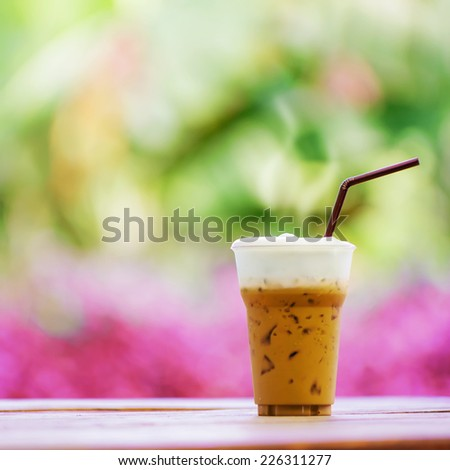 Iced coffee with straw in plastic cup on a wooden table in summer with Nature background. - stock photo