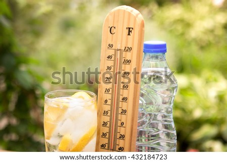 Iced glass water and thermometer that shows high temperature  - stock photo