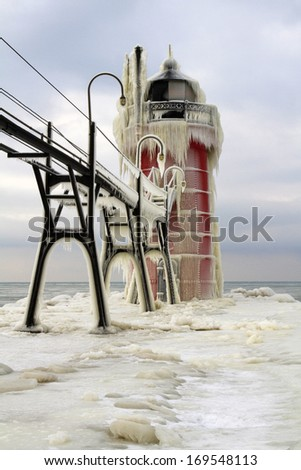 Iced Over -- The South Haven Lighthouse freezes over during the early part of winter. South Haven, Michigan, USA. - stock photo