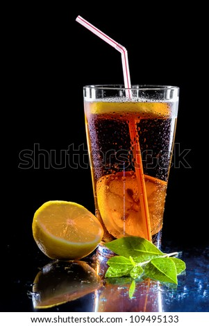 Iced tea and green leaf isolated on  black background - stock photo