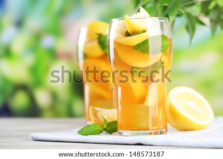Iced tea with lemon and mint on wooden table, outdoors - stock photo