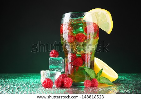 Iced tea with raspberries and mint on dark background with green light - stock photo
