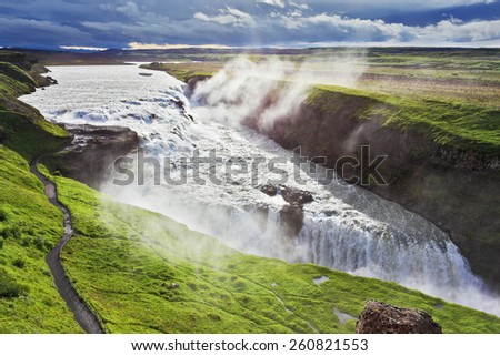 Iceland. Grand Gullfoss. In mid-July, bubbling water illuminated by a bright morning sun - stock photo