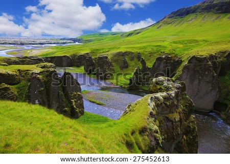 Iceland in July. Canyon Fjadrargljufur and cold fast river with a pebble bottom - stock photo