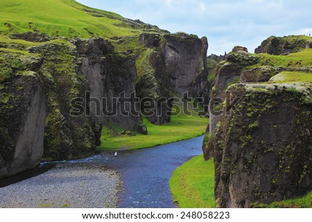 Iceland in the summer. Canyon Fjadrargljufur and cold fast river with a pebble bottom - stock photo