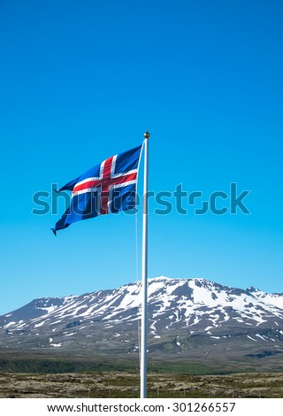 Icelandic flag waving in front of some mountains - stock photo