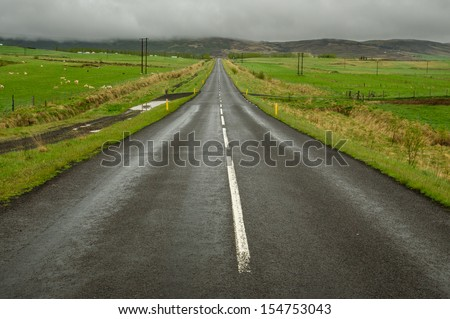 Icelandic road through farms in light rain - stock photo