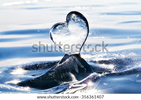 Icicle in the form of heart on the ice of Lake Baikal. From Siberia with love. Cold heart. Love of nature. Blue ice on the surface of Lake Baikal, Siberia, Russia. Horizon. Winter. Macro photo. - stock photo
