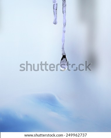 Icicle with drop of water on blue, pink and and purple background - stock photo