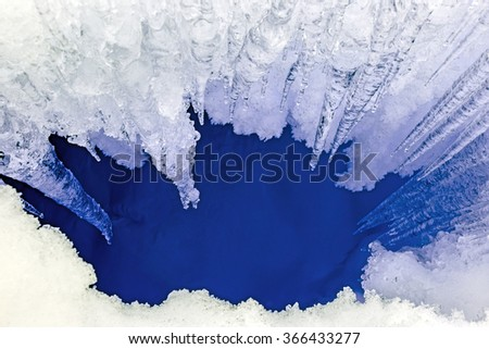 Icicles and deep crack in the ice - stock photo