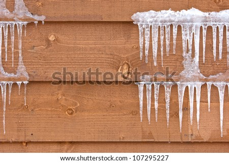 Icicles hang from a wood cabin in on a chilly winter day - stock photo