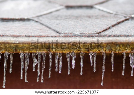 icicles hanging down from a roof - stock photo