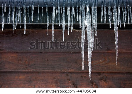 Icicles hanging from a drainpipe on the exterior of a wooden panelled house. - stock photo