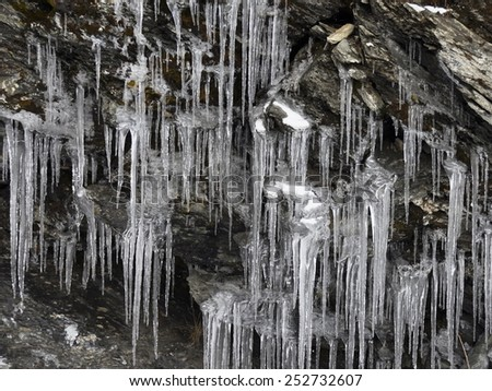 Icicles hanging from a stone ledge - stock photo