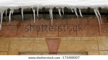 Icicles hanging from the roof of a house. - stock photo
