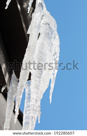 Icicles hanging off a roof in the sunlight - stock photo
