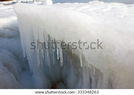 Icicles on the ice, sea a block of ice on the sea, the ice in the icicles, winter in seas and oceans, Arctic aquatic nature, the ice floe in the ocean, the melting of ice. - stock photo