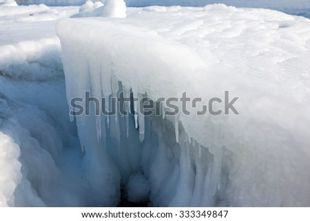 Icicles on the ice, the sea a block of ice on the sea, the ice in the icicles, winter in seas and oceans, Arctic aquatic nature, ice in the ocean, melting of ice. - stock photo