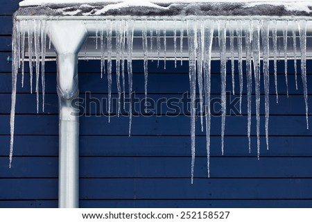 Icicles on the roof. Winter concept. downspout. Blue wooden background. - stock photo
