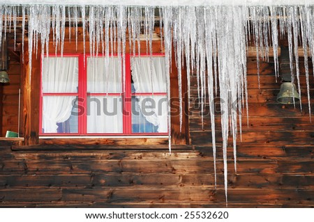 Icicles on wooden house - stock photo