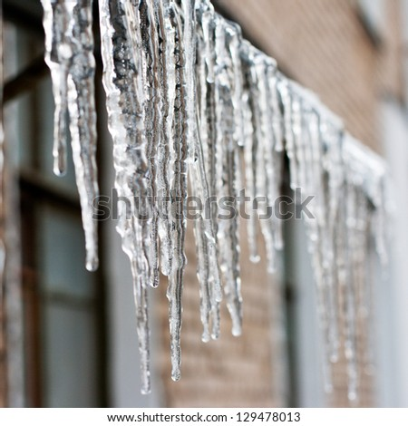 icicles which are hanging down from a roof. - stock photo