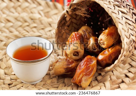 Iconic Abrian fabric is graced with sybbols of Arabia, in particular Arabic tea and dates, they symbolise Arabian hospitality. - stock photo