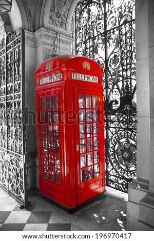 Iconic British red telephone box and beautiful metal gate lace - stock photo