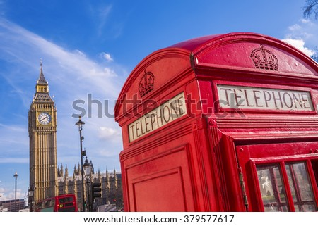 Iconic British red telephone box with Big Ben and Double Decker bus at background on a sunny day with blue sky - London, UK - stock photo