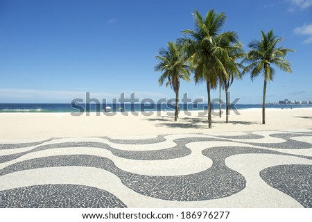 Iconic sidewalk tile pattern with palm trees at empty view of Copacabana Beach Rio de Janeiro Brazil  - stock photo