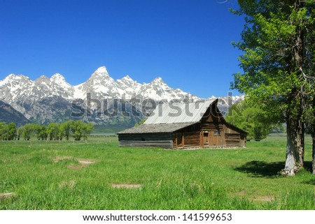 Iconic view of a rustic barn with the Teton mountain range in the background, Wyoming, USA. - stock photo