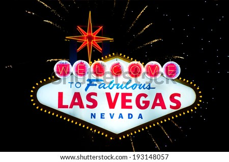 Iconic Welcome to Fabulous Las Vegas sign with fireworks in the back  - stock photo