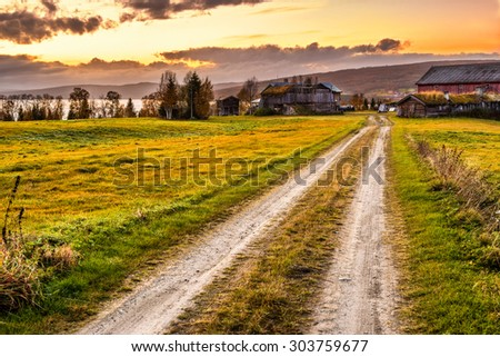 Iconic wooden barn with farmhouse and rural path at sunset in Norway - stock photo