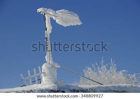 Icy antenna on mountain weather station - stock photo