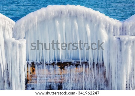 Icy Arch with Icicles on a Background of the Sea - stock photo