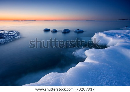 Icy beach and cold open water in the coast of Helsinki, Finland in early morning. - stock photo
