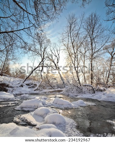 Icy river in winter sunny day, with sunbeams through branches trees.   - stock photo
