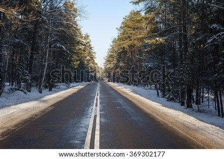 Icy road in a sunny winter day - stock photo