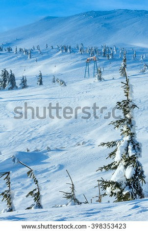 Icy snowy fir trees and ski lift on winter morning slope. - stock photo