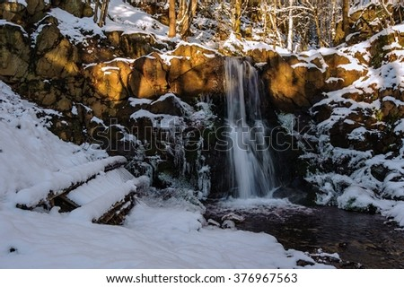 Icy waterfall in the frosty forest with snow - stock photo