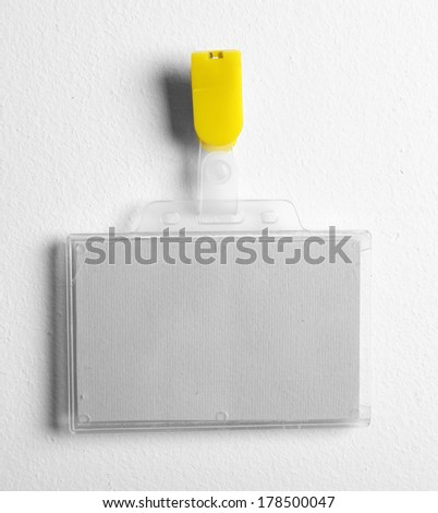 Id badge on white wall - stock photo