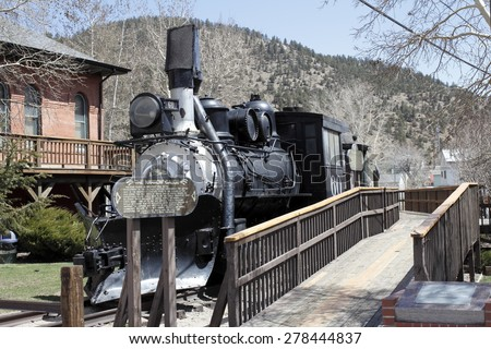 Idaho Springs, CO, USA - April 23, 2014: Front and side view of an old black train with historical information on a wood sign. A wooden walkway travels the length of the historical train   - stock photo