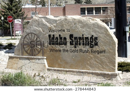 Idaho Springs, CO, USA - April 23, 2014: Large tan stone that has written on and carved into it, Welcome to Idaho Springs, Where the Gold Rush Began! The sign has a brown sculpture of a water wheel - stock photo