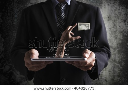 Idea and concept of business man holding a tablet and thief hand breaking a screen to stealing a money. With clipping path. - stock photo