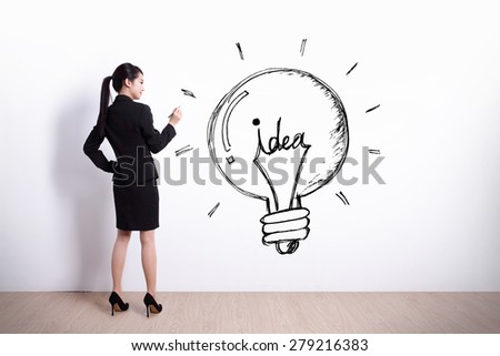 idea concept - Back view of business woman writing idea and light bulb on white wall background - stock photo