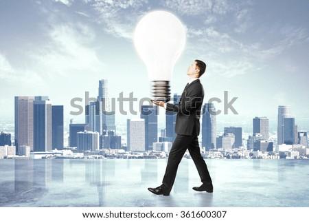 Idea concept, businessman carries a light bulb - stock photo
